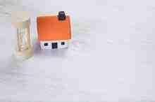 Modell eines kleinen Hauses mit Stundenglas