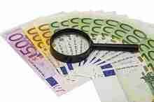 Beitragsbild: 14000 Euro in Scheinen unter einer Lupe