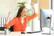 Junge Frau am Computer erfreut über günstigen Kreditabschluss