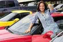 Junge Frau steigt in ein rotes Auto ein. Sie konnte ihr Auto günstig finanzieren.