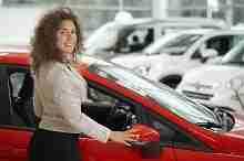Eine junge Kundin beim Autohändler