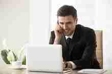 Kreditkunde am Laptop telefoniert mit der Deutschen Bank zur Vorbereitung einer Kreditaufstockung