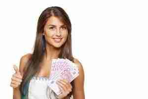Junge Frau mit Euroscheinen in der Hand lächelt nach erfolgreichem Kreditabschluss