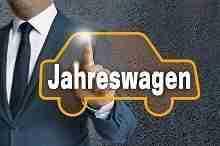 Eine Person klickt auf einen Touchscreen, der ein Auto mit der Aufschrift Jahreswagen abbildet.