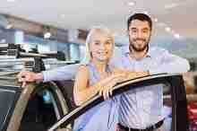 Junges Paar vor ihrem neuen Kleinwagen