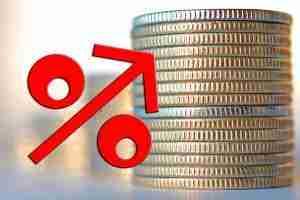 Ein Stapel Münzen mit einem nach oben gerichteten Pfeil ausgestatteten roten Prozentzeichen im Vordergrund. Kreditkosten steigen durch Zahlpausen.