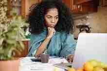 Junge Frau mit Unterlagen am Laptop in Vorbereitung eines Antrags zur Kreditaufstockung bei der Postbank