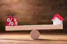 Würfel mit Prozentsymbol und kleines Haus auf einer hölzernen Waage. Welche Sollzinsbindung soll man wählen?