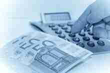 Rechner und Euroscheine: Aufstockungskredit oder Umschuldungskredit